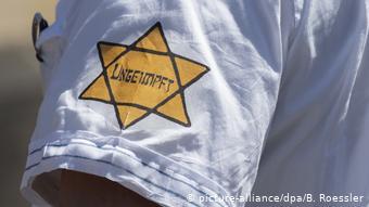 Ένας από τους διαδηλωτές κατά των περιοριστικών μέτρων του κορωνοϊού με το εβραϊκό αστέρι στο μανίκι του