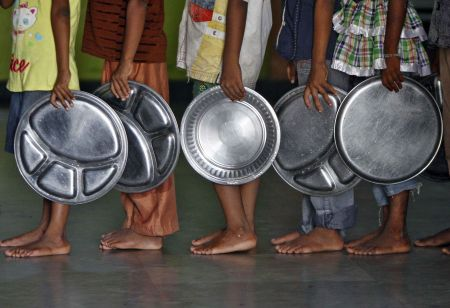 Children holding plates wait in a queue to receive food at an orphanage run by a non-governmental organisation on World Hunger Day, in the southern Indian city of Chennai