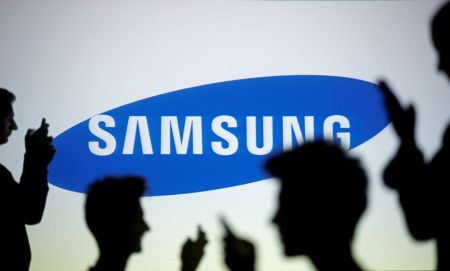 FILE PHOTO - People pose with mobile devices in front of projection of Samsung logo in this picture illustration